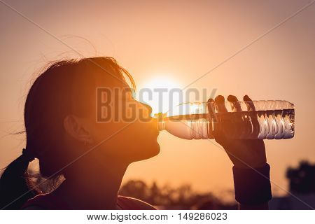 Female drinking a bottle of water on sunset.