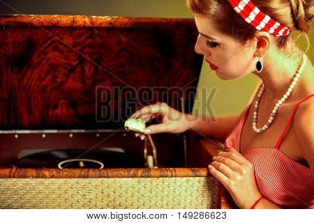 Girl in style keeps vinyl record. Pin-up retro female style. Girl pin-up style wearing red dress. Girl is going to listen to music.