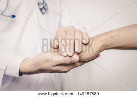 Two people holding hands for comfort vintage tone. doctor's hands holding patient's hand for encouragement and empathy. Doctor man. Doctor woman. Doctor hand. Doctor room. Uniform doctor. Doctor shake hand.