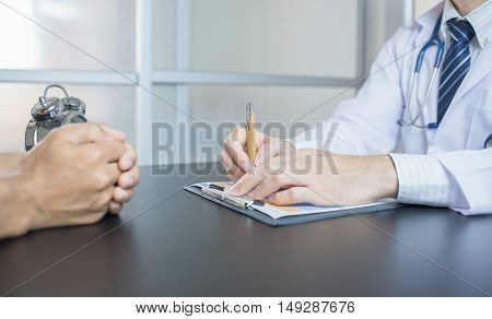 close up of patient and doctor taking notes. Doctor man. Doctor woman. Uniform doctor. Doctor writting. Doctor looking. Doctor room.