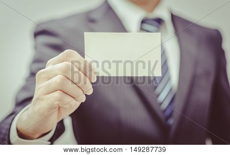 Man's hand showing business card - closeup sho vintage tone. Card in hand business. Uniform business. Business working.