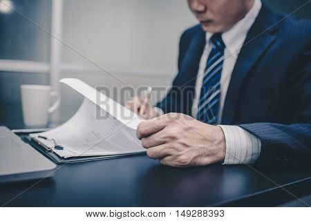 Business man signing a contract . Close-up photo vintage tone. Business writting. Business looking. Business reading. Business working.
