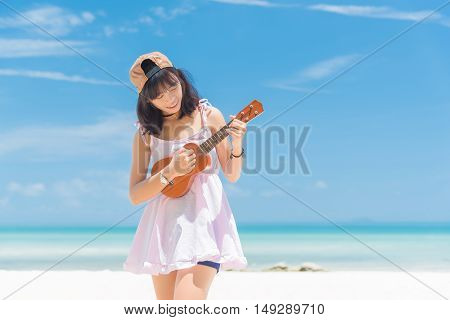 Women playing ukulele at the beach. Asia girl at beach from Thailand. Beautiful young woman playing ukulele at sea on blue sky.