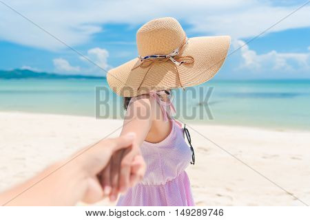 Woman walking on romantic honeymoon beach holidays holding hand of boyfriend following her view from behind. A young girl holding hands on the beach.