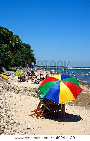 STUDLAND BAY, UNITED KINGDOM - JULY 19, 2016 - Holidaymakers relaxing on the beach with a colourful parasol in the foreground Studland Bay Dorset England UK Western Europe, July 19, 2016.
