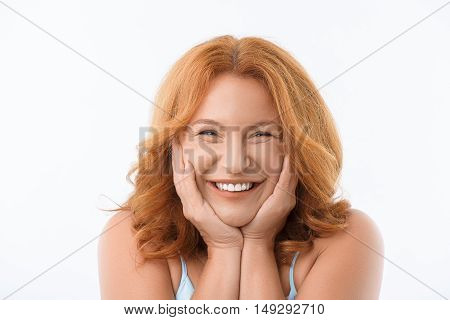 I am so happy. Cheerful middle-aged lady is looking at camera and smiling. She is standing and touching her head prettily. Isolated