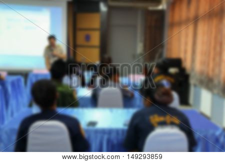 focus blur blurred student learning business sitting in room with teacher front and white projector slide screen  blurred view from back of the classroom