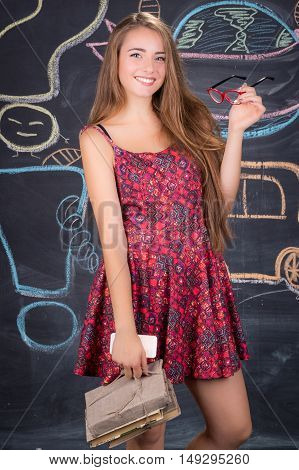 Young student girl in red dress with red glasses and pack of books poses in front of school classroom blackboard