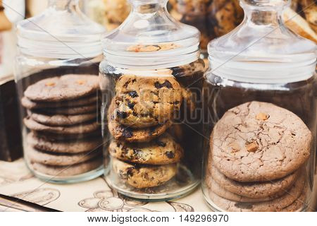 Desserts choice. Cookies and biscuits in glass jars on counter bar for sale. Chocolate drops and chips, oatmeal cookies stacks.
