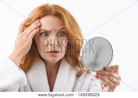 Again new wrinkle. Terrified middle-aged woman is looking at mirror and touching her facial skin with frustration. She is standing in bathrobe. Isolated