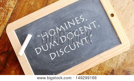 Homines dum docent discunt. A Latin phrase, usually translated into English as Men learn while they teach.