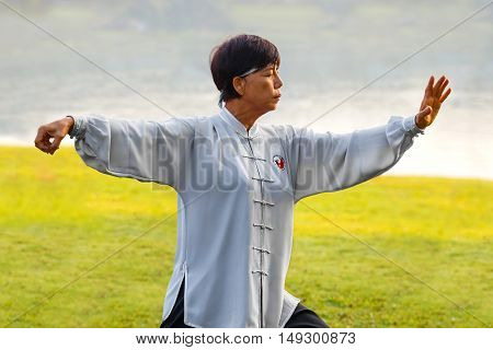 BANGKOK THAILAND - FEBRUARY 13 2016: Unidentified group of people practice Tai Chi Chuan - Chinese exercising martial arts in a park