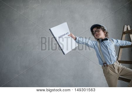 Boy with a screenplay on stairs