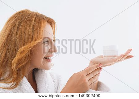 Cheerful middle-aged woman is holding cream can and looking at it with satisfaction. She is standing in bathrobe and smiling happily. Isolated