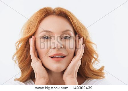Red-haired middle-aged woman is satisfied with her taut skin. She is touching face and smiling. Isolated
