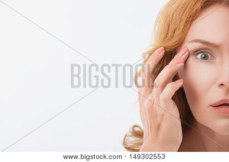 Close up of half female face. Woman is touching wrinkle in eye area and looking at camera with shock. Isolated and copy space in left side