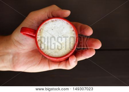 red cup of frothy cappuccino on a palm a top view / warms coffee with whipped milk