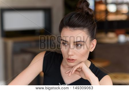 close up of a thoughtful woman in a cafe