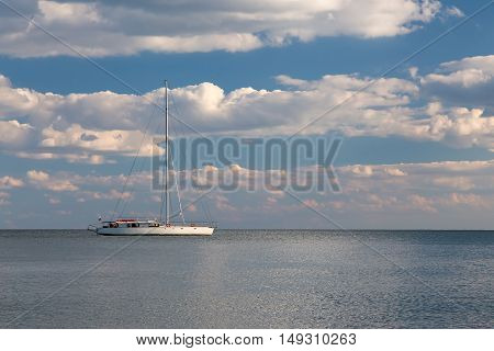 White yacht with deflated sails. Blue sky with clouds and calm sea