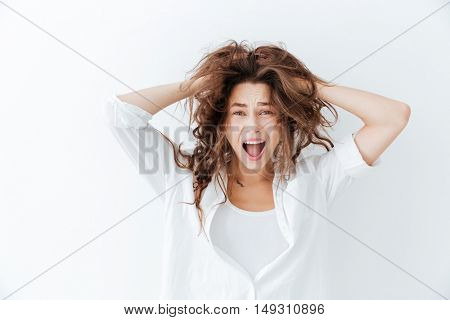 Young brunette woman with long hair shouting isolated on a white background