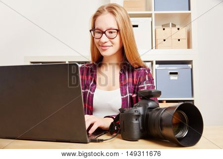 Photographer with DSLR Camera and Laptop in her office