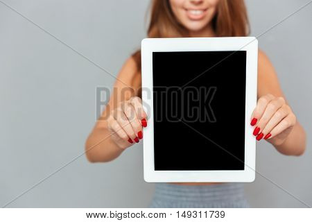Smiling charming young woman holding blank screen tablet over grey background