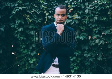 Making a face. Handsome young African man in smart casual wear holding hand on chin and making a face while standing against green plant background outdoors