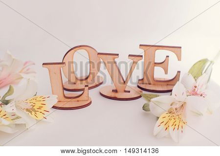Decorative letters forming word LOVE with wildflowers on wooden background.