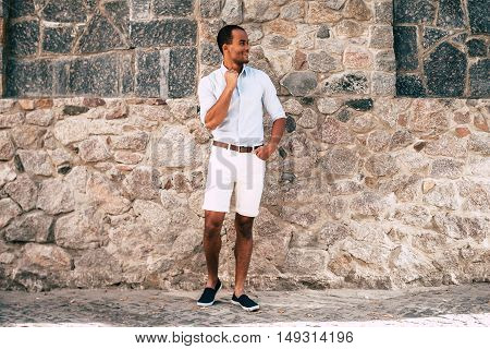 Stylish handsome. Full length of cheerful young African man in smart casual clothes standing against the stoned wall outdoors