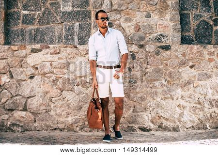 Cool and in style. Full length of handsome young African man in smart casual clothes carrying bag and looking away while standing against the stoned wall outdoors