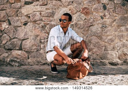 Confident in his perfect style. Handsome young African man in smart casual clothes crouching near his bag and with stoned wall in the background