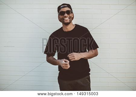 Stay real! Handsome young African man in black T-Shirt smiling and looking at camera while standing in front of the brick wall outdoors
