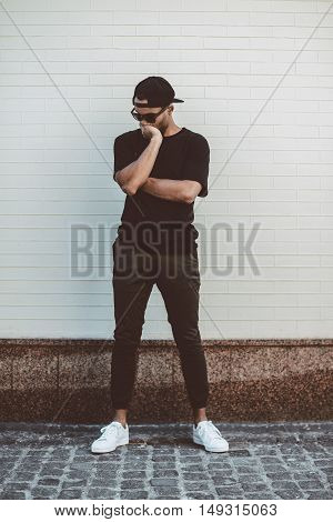 Lost in thoughts. Full length of young mixed race man in casual clothes standing in front of the brick wall and covering face with hand