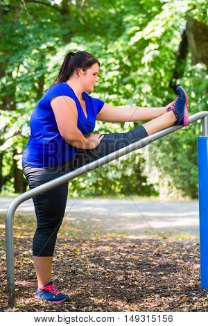 Obese woman doing sport stretching outdoors in park
