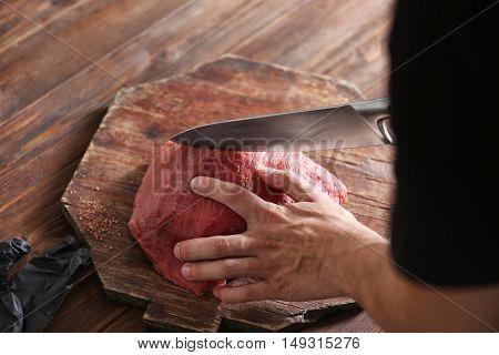 Butcher cutting pork meat on kitchen