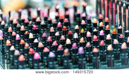 Beautiful big multicolor professional makeup set of many different colorful lipsticks in black plastic tubes in show case horizontal picture