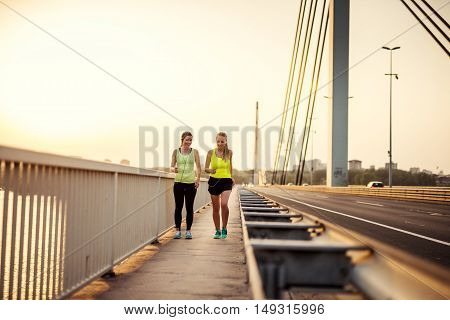 Two young girls enjoying jogging together outdoors.