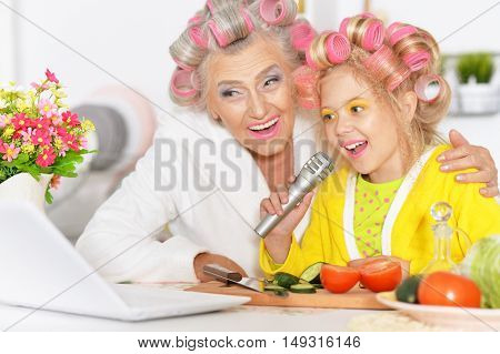 Senior woman and granddaughter at kitchen with  vegetables and laptop
