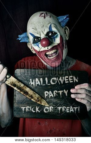 a scary evil clown pointing a big knife at a wore chopping board with the text Halloween party trick or treat written in it