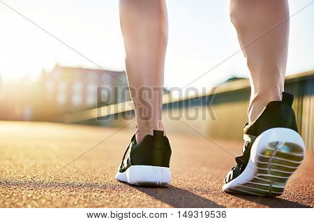Bare legs in running shoes preparing to exercise on a bright summer day on an empty road