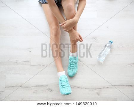 Woman wearing mint sneakers on wooden floor background