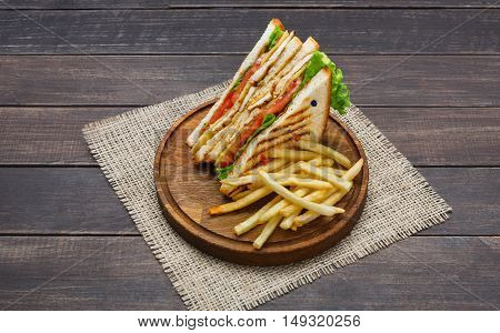 Fast food meals at sandwich bar. Chicken and vegetables sandwich and potato chips on wood. Take away composition. French fries with snack on wooden desk.