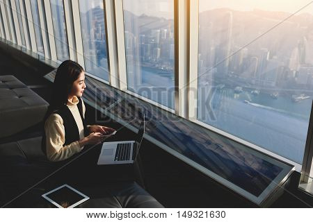 Female CEO with mobile phone in hands and open laptop computer is looking in office window on view Honk Kong city. Woman manager is using gadget while is sitting in interior with contemporary design