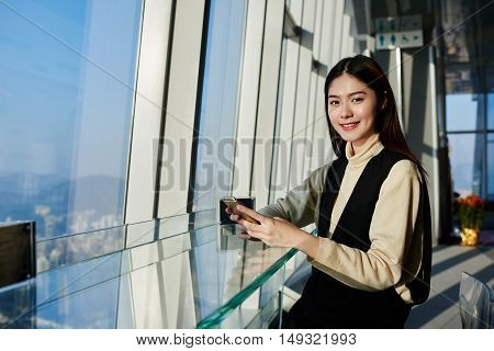 Charming Chinese hipster girl with cell telephone in hands is smiling for the camera while is sitting in loft with contemporary design and big window with view of metropolitan city in Honk Kong