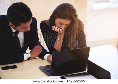 Two professional programmers are working together on a new projector via portable laptop computer while sitting in co-working space. Young man and woman are searching information via net-book