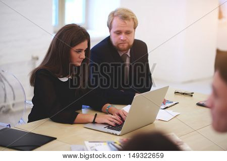 Woman skilled jurist is keyboarding on laptop computer while is sitting with partner in modern co-working space. Attractive manager is searching information on net-book during consultancy with client