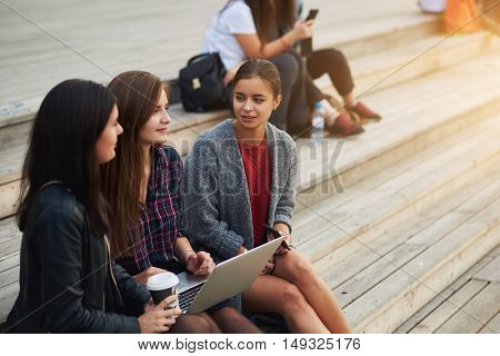 Three students are talking about future exam in university while are sitting with net-book on a campus. Beautiful hipster girls are enjoying rest while are waiting file download on laptop computer