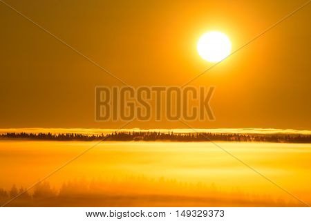 Sunrise and lot of mist in autumnal landscape