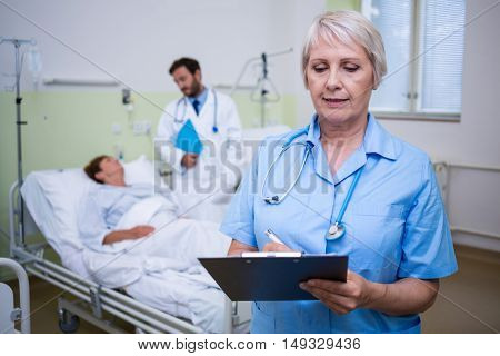 Nurse writing on clipboard in hospital room