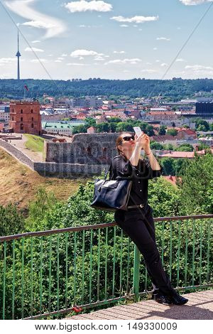 Vilnius, Lithuania - June 16, 2016: Woman making selfie with Gediminas Tower on the hill and the Lower Castle down the hill in Vilnius in Lithuania. The Tower is also called as Upper Castle. Lithuania is a Baltic country